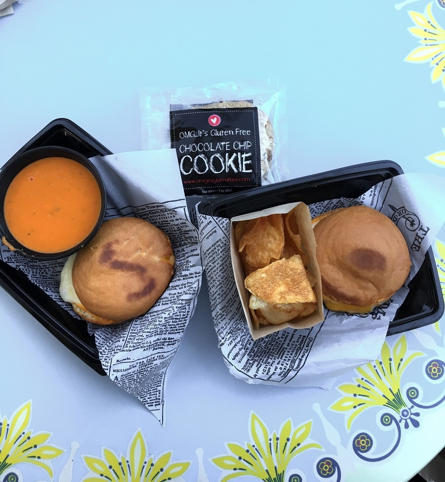 two trays with a grilled cheese sandwich on round shaped bread next to a bowl of tomato soup, and a gluten free chocolate chip cookie in a package