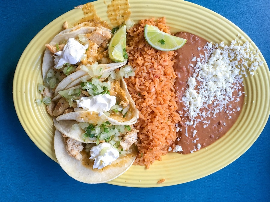 a yellow plate filled with three tacos, mexican rice, and refried beans