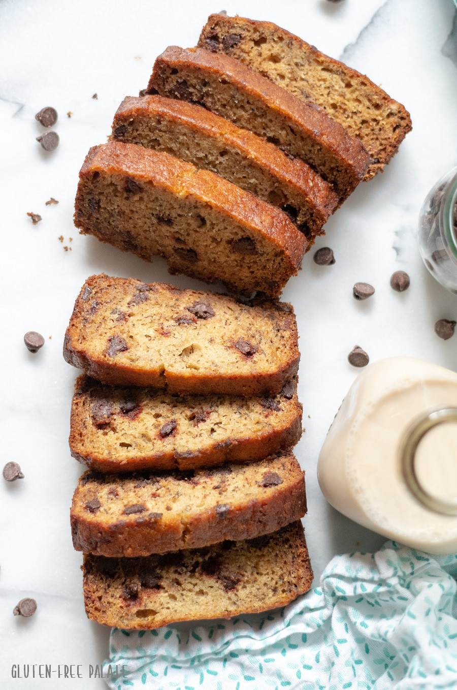 slices of Gluten-Free Banana Bread with scattered chocolate chips and a jar of milk