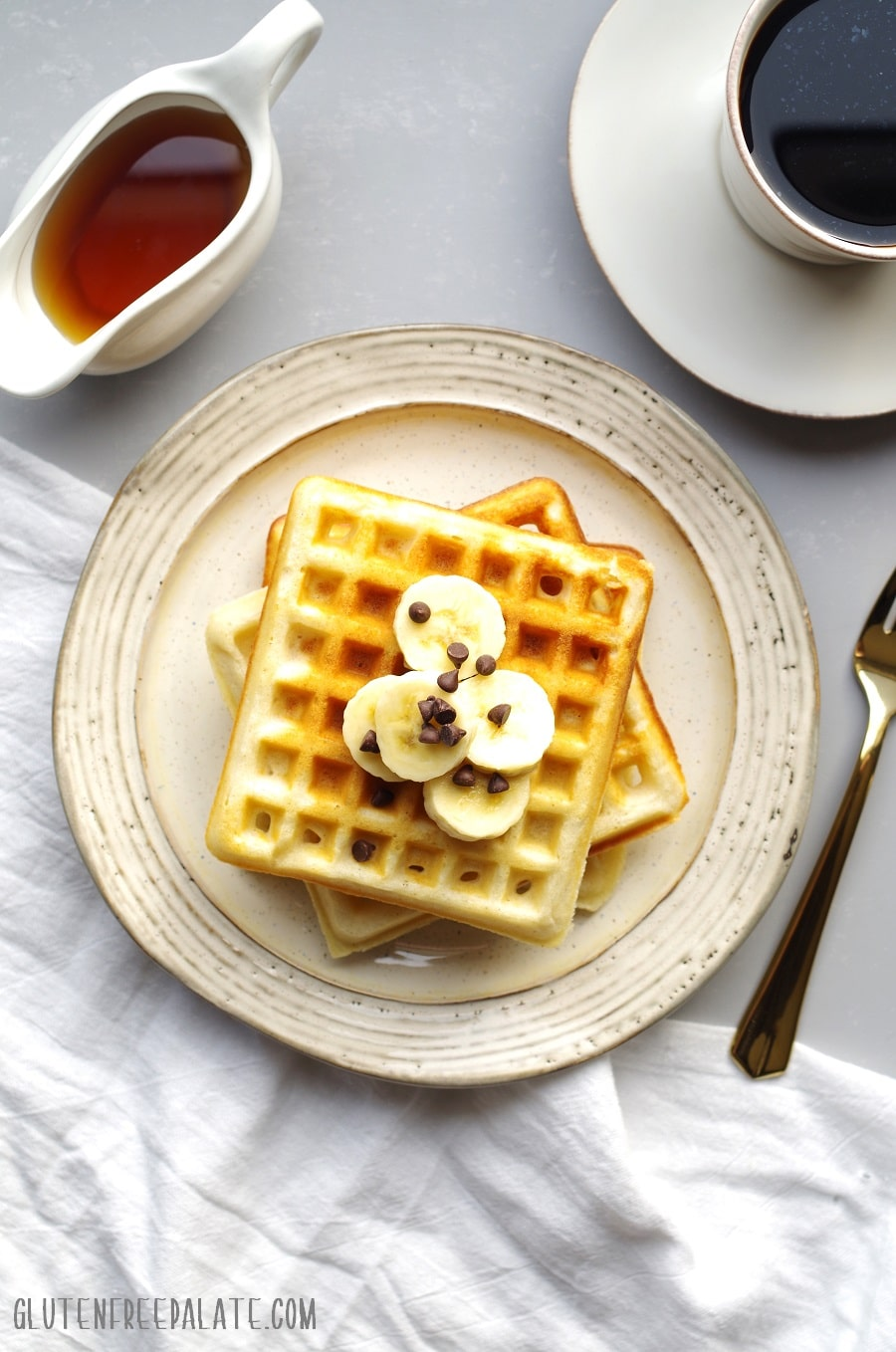 top down view of three waffles stacked on a cream colored plate, topped with sliced bananads next to a cup of coffee and container of maple syrup