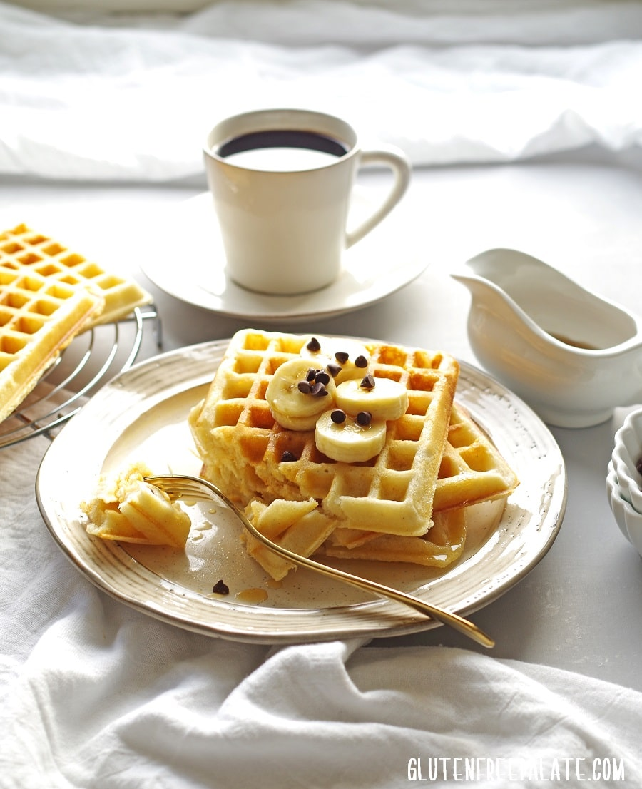 three waffles on a cream colored plate with a bite taken out on a fork, a cup of coffee in the background