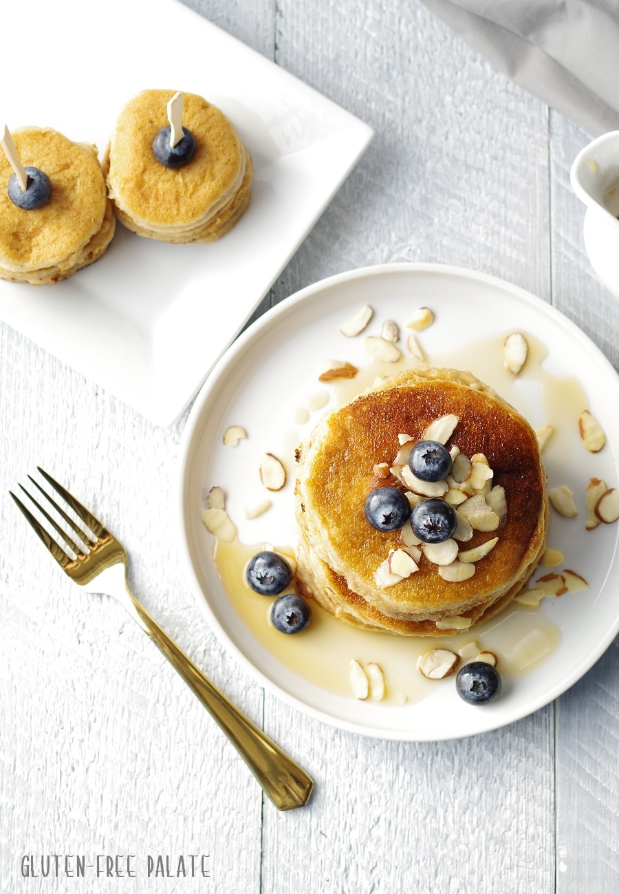top down view of pancakes stacked on a white plate, topped with blueberries, sliced almonds and maple syrup