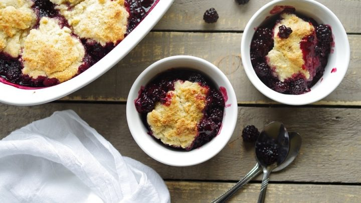 two bowls of gluten free blackberry cobbler next to a white napkin