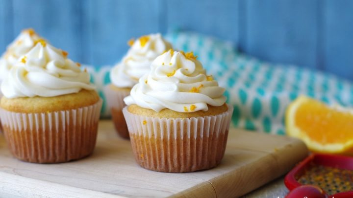 three gluten free orange cupcakes topped with frosting and orangezest
