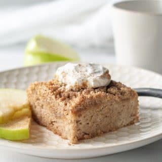 a slice of paleo apple cake with whipped cream on top, on a white plate with sliced apple