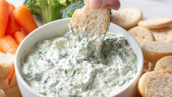 a hand dipping a slice of bread into a bowl of spinach dip, next to broccoli and carrots and bread slices