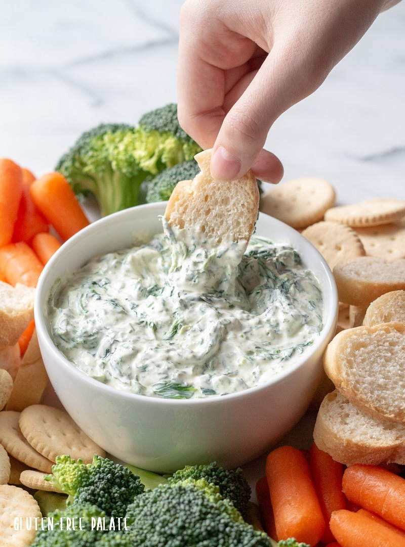 a hand dipping bread into a bowl of spinach dip