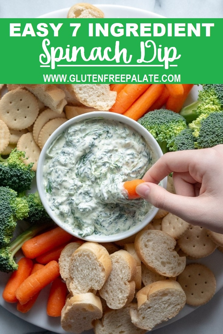 a hand dipping a corrot into a bowl of spinach dip with the words easy 7 ingredient spinach dip written in text at the top