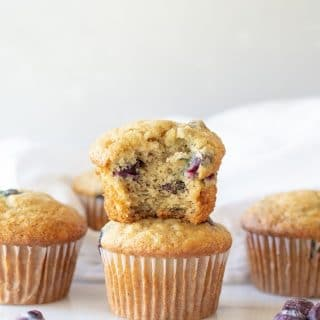 Gluten Free Blueberry Banana Muffins stacked on top of one another, one has a bite out, they are stacked near three other muffins and scattered blueberries