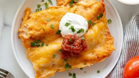 two enchiladas with cheese, sour cream, and salsa on a white plate next to a two tomatoes and a bowl of salsa and sour cream