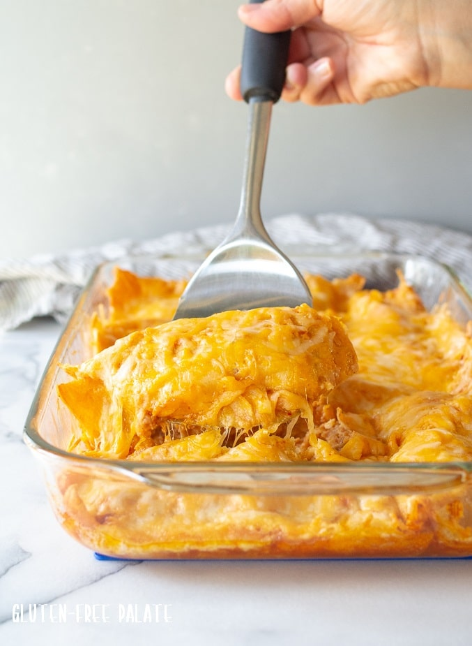 a spatula lifting a cheesy enchilada out of a glass pan