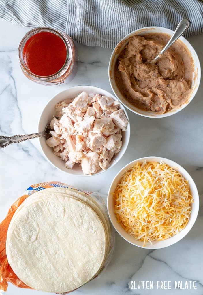 a stack of corn tortillas, a bowl of shredded chicken, a bowl of shredded cheese, a bowl of refried beans, a jar of enchilada sauce