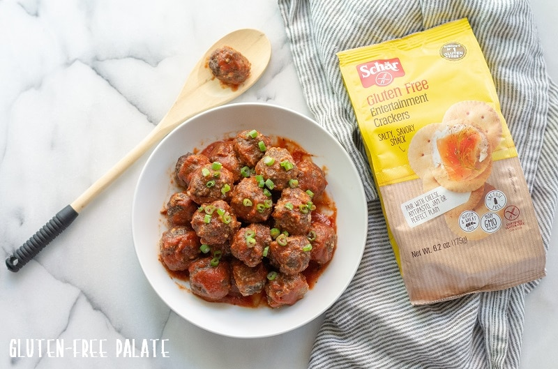 Gluten-Free Meatballs covered in marinara sauce and chopped green onions, on a white plate, next to a bag of schar crackers