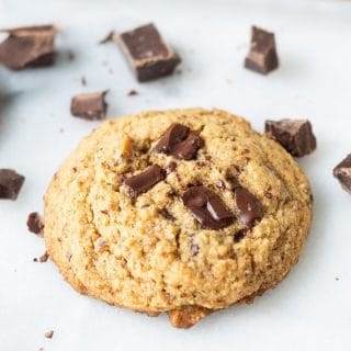 Paleo Chocolate Chip Cookie on a white background with chunks of chocolate around it