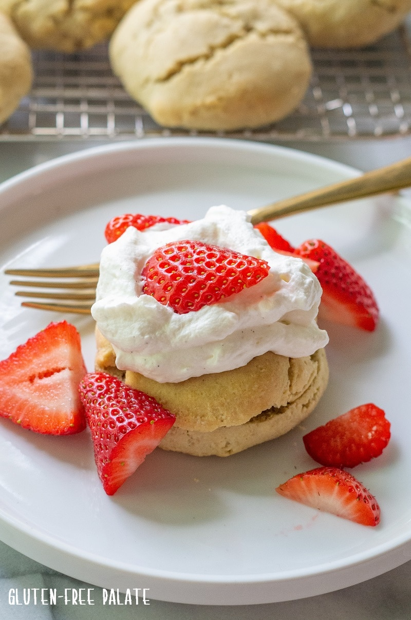 shortcake on a white plate topped with whipped cream and strawberries and a gold fork
