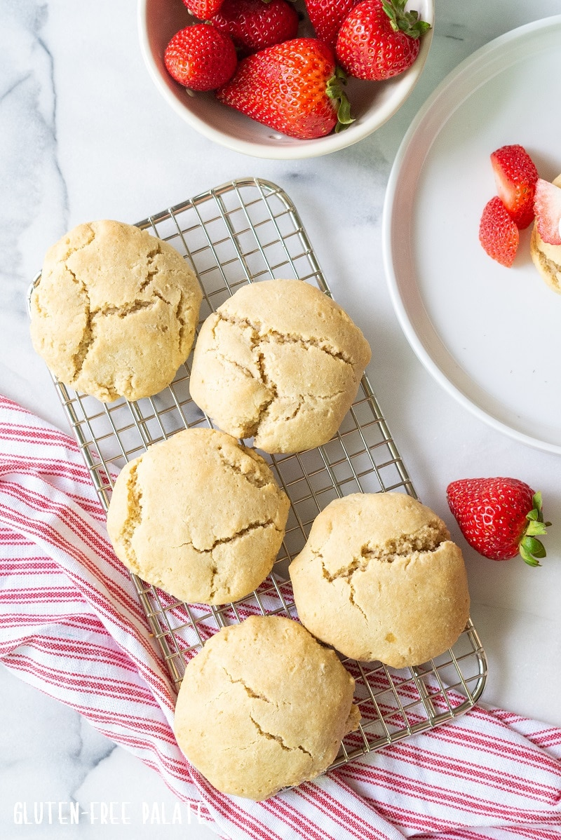 shortcakes on a wire cooling rack over a white and red towel next to a bowl of strawberries