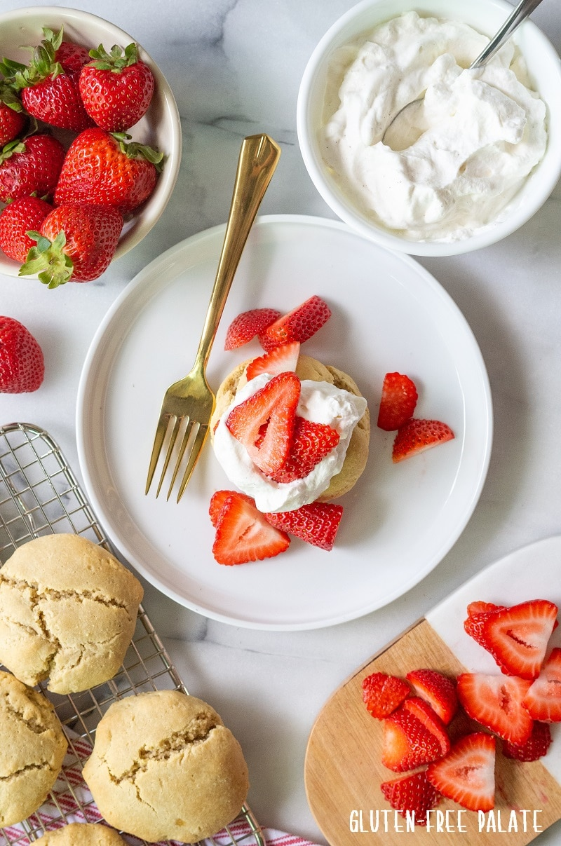 Paleo Strawberry Shortcake on a white plate with sliced strawberries with strawberries, whipped cream and shortcakes around it