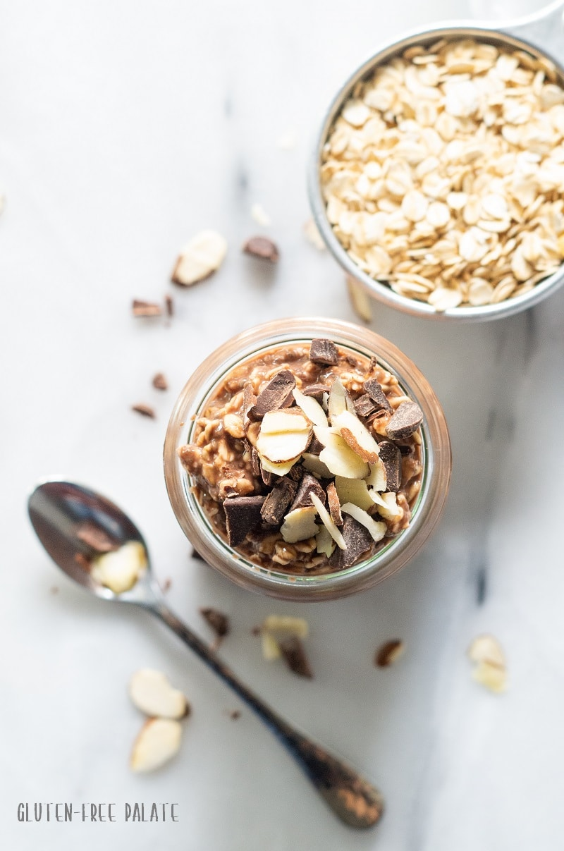 top down view of chocolate overnight oats in a glass jar next to a bowl of dried oats and a spoon