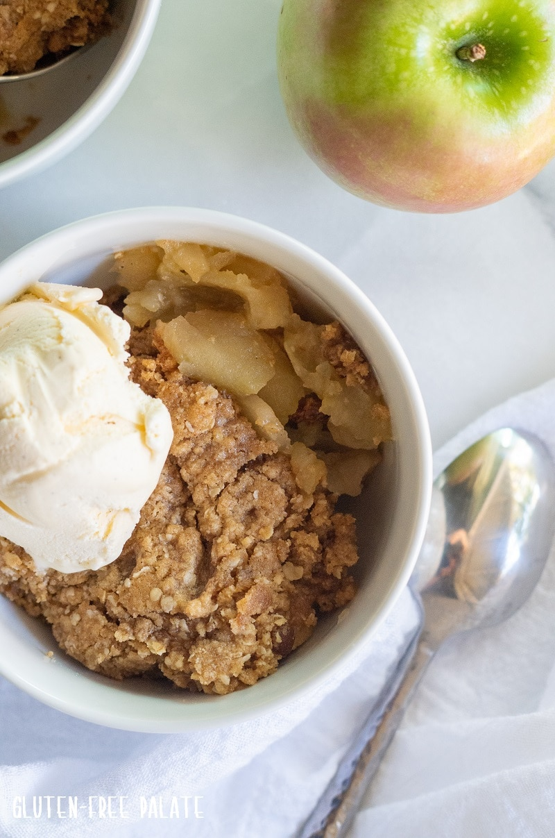 Gluten free apple crisp in a white bowl with ice cream on top, a spoon and a green apple are next to it