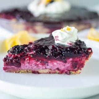cream cheese pie with blackberries on a white plate, topped with whipped cream
