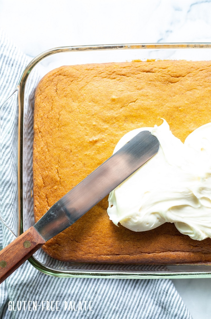 a knife spreading white frosting on gluten free pumpkin cake in a glass baking pan