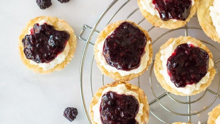 gluten free lemon blackberry tarts on a wire cooling rack next to a jar of blackberry topping