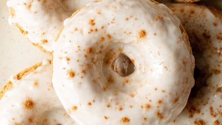 close up of gluten free apple cider donuts with white icing and cinnamon sprinkled on top on a cream colored plate