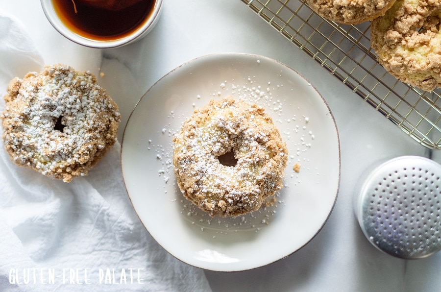 Gluten Free Crumb Donut sprinkled with powdered sugar on a white plate next to a donut, a cup of coffee and a cooling rack