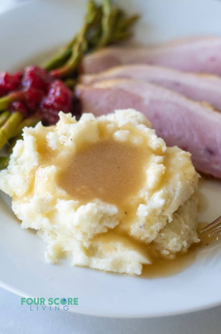 mashed cauliflower topped with brown keto gravy on a white plate with cranberry sauce and ham
