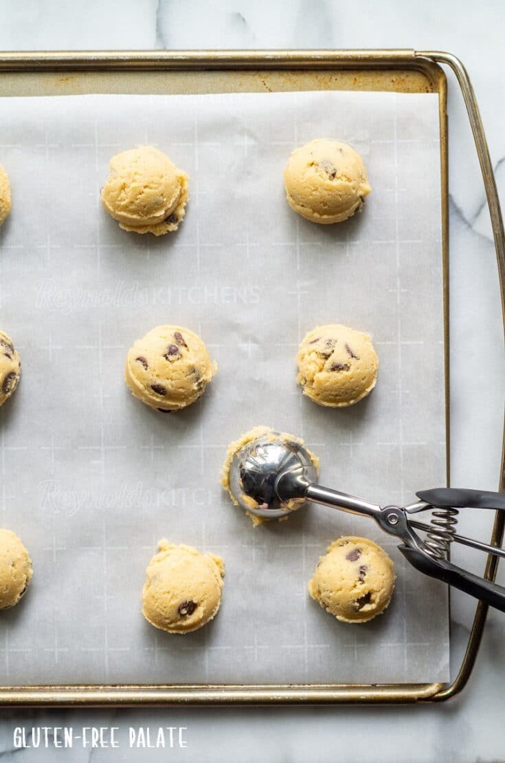 gluten free chocolate chip cookie dough on a sheet pan with a cookie scoop