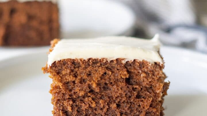 a slice of borwn Gluten Free Gingerbread Cake with white frosting on a white plate
