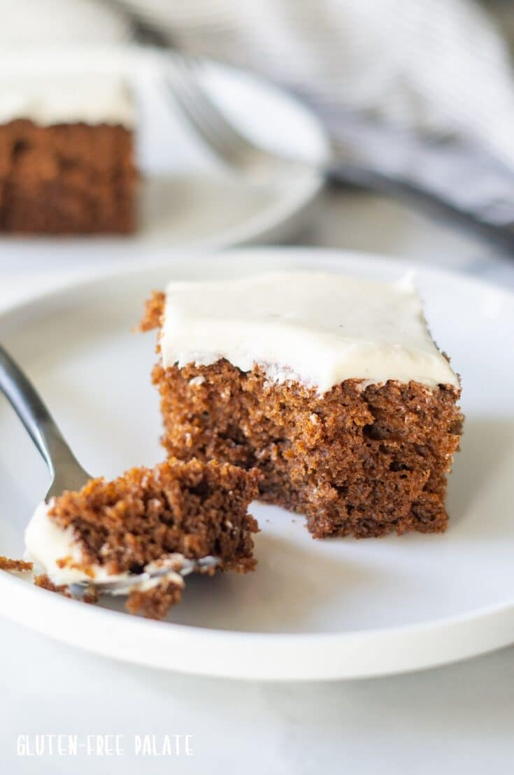a slice of brown Gluten Free Gingerbread Cake with white frosting on a white plate with a fork taking a bite out