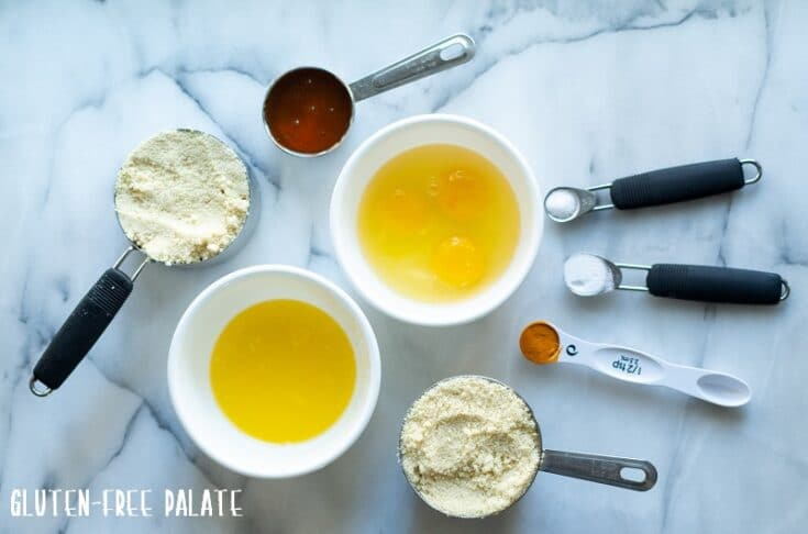 ingredients in paleo cornbread, almond flour, maple syrup, eggs, melted butter, turmeric, salt, baking powder