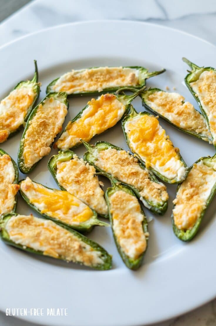 jalapeno poppers with melted cheese and cracker crumbs on top, on a white plate