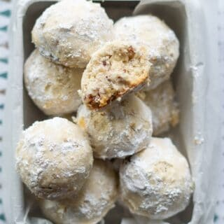 gluten free snow ball cookies in a square metal tin lined with wax paper, one cookie has a bite out