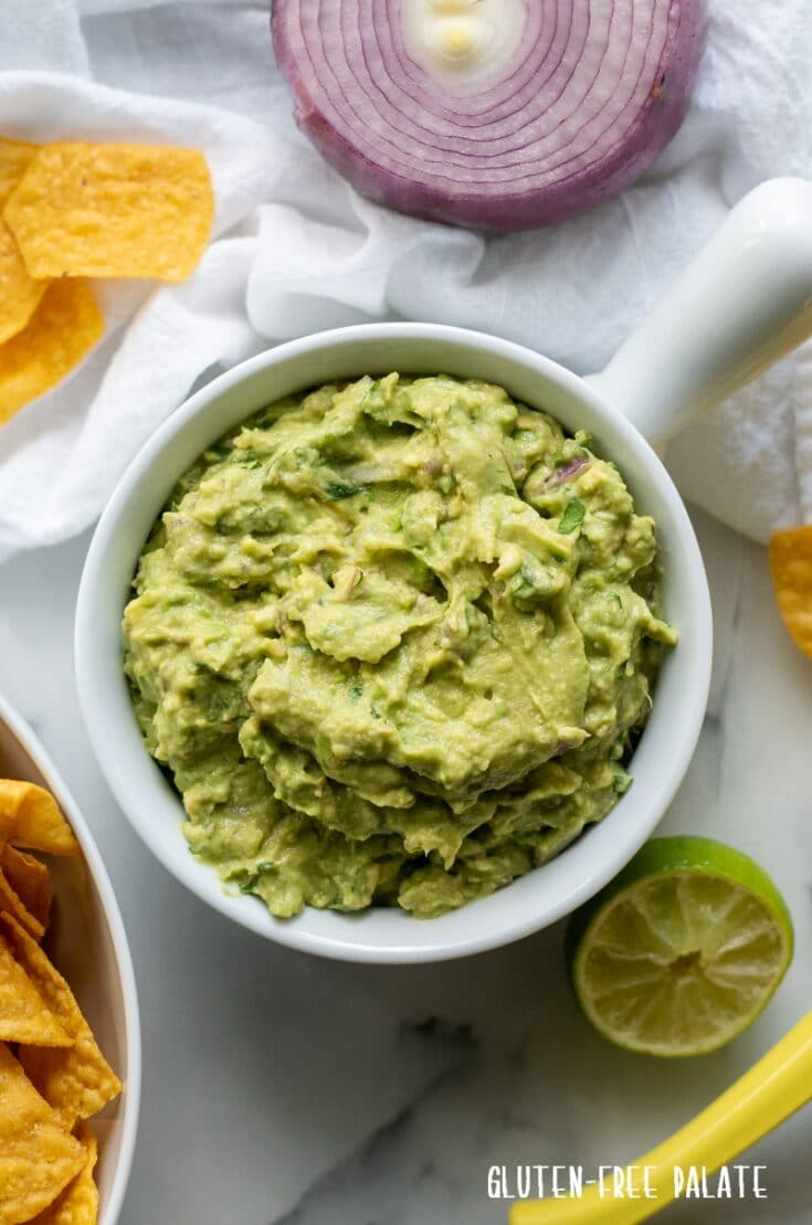 guacamole in a white bowl surrounded by red onion and yellow chips and a lime wedge