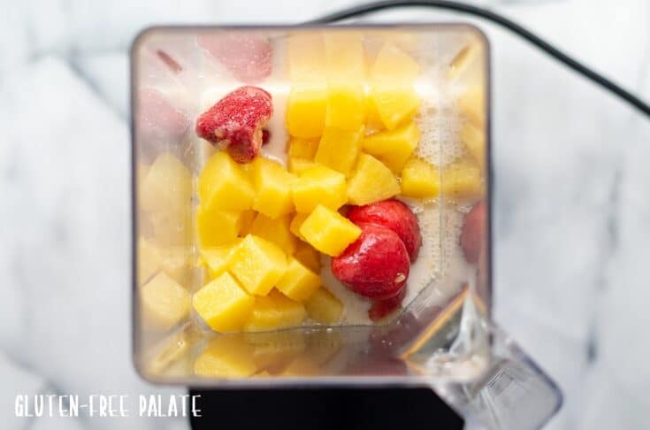 blender jar with pineapple chunks, strawberries and almond milk