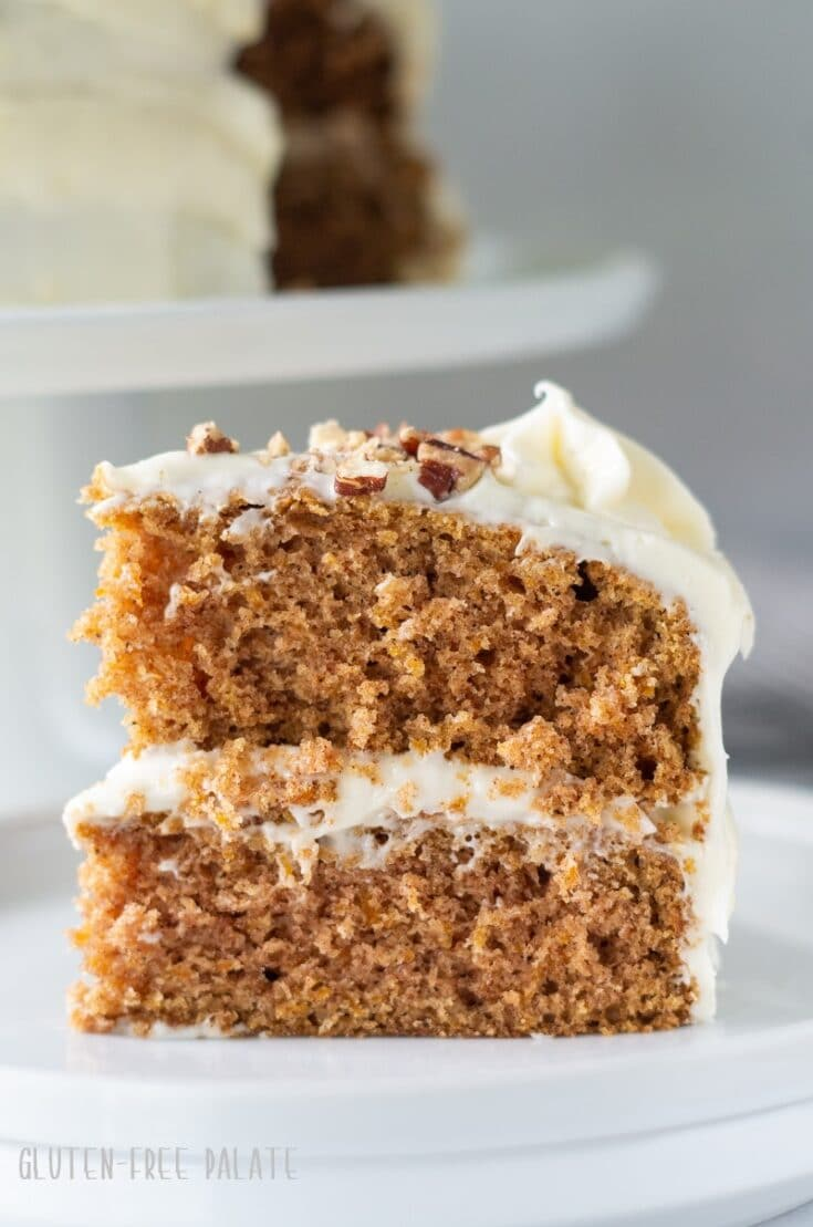close up of a slice of gluten free carrot cake topped with frosting and chopped nuts on a white plate
