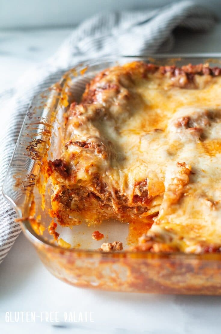 a side view of gluten free lasagna in a glass baking pan showing the layers in lasagna