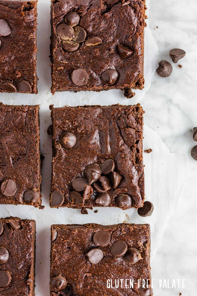 a close up of sliced flourless brownies topped with chocolate chips