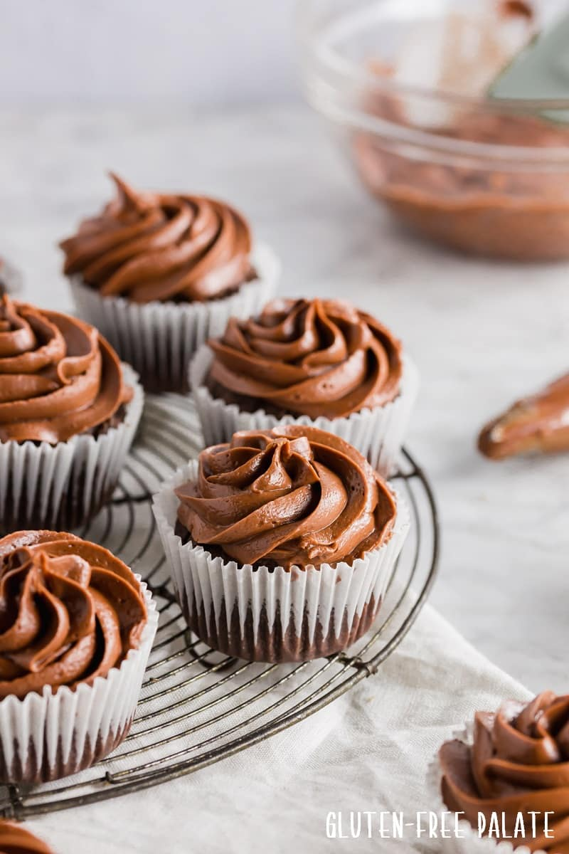 chocolate cupcakes in white paper liners topped with chocolate frosting, on a wire cooling rack