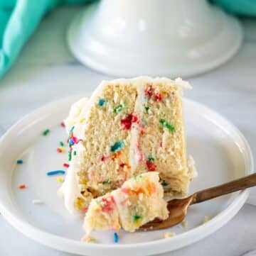 a slice of gluten free funfetti cake on a white plate with a gold fork
