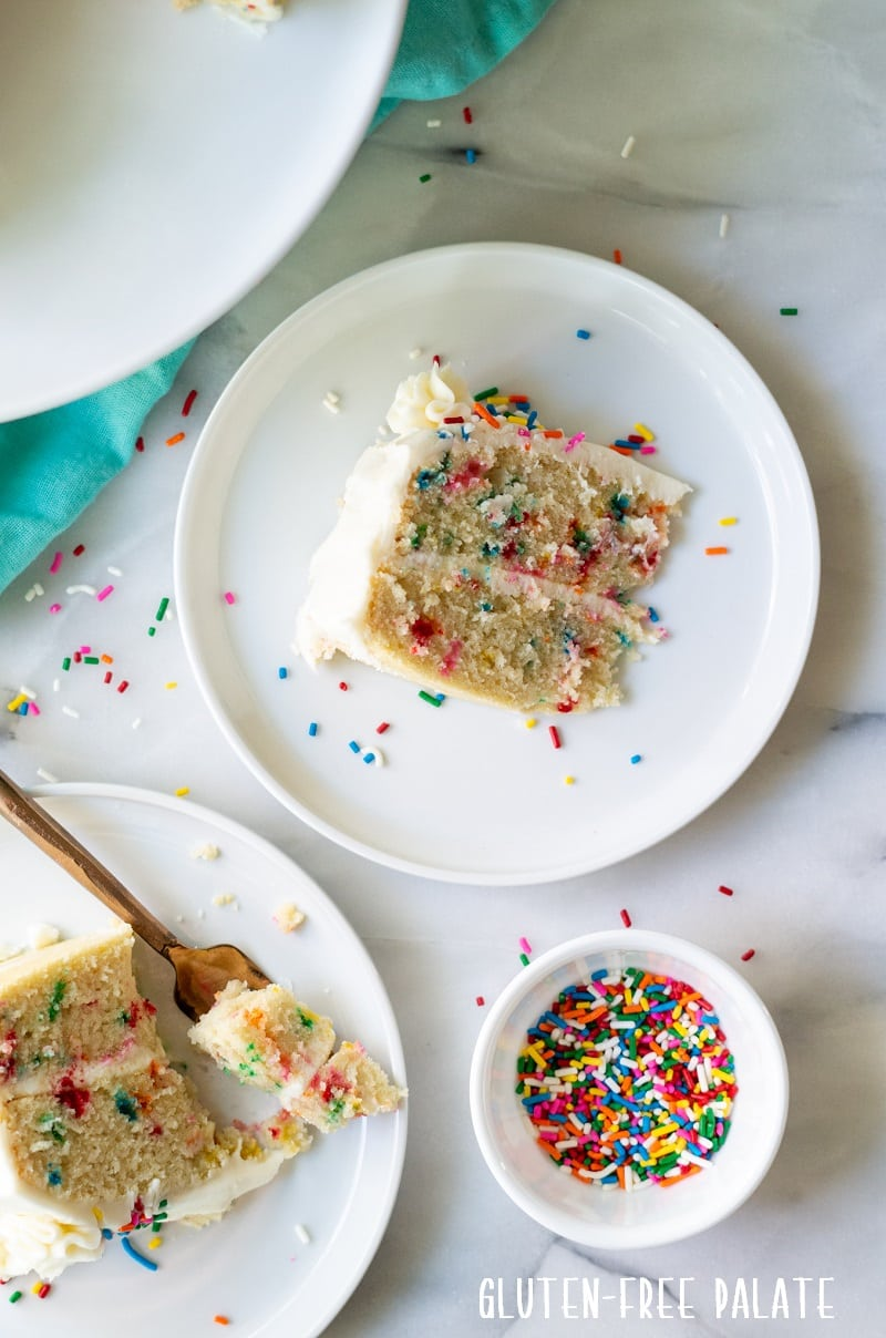 slices of funfetti cake on a white plate next to a bowl of sprinkles