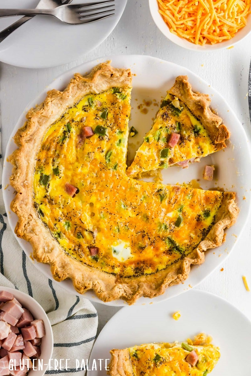 gluten free quiche in a white pie pan with a slice out
