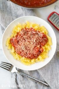 spaghetti sauce over noodles in a white bowl