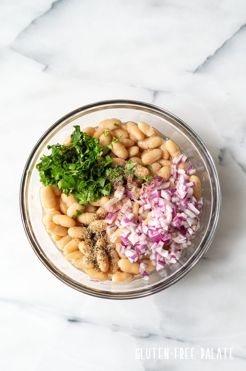 ingredients in white bean salad in a clear bowl, before mixing together