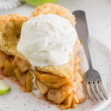 a close up of a slice of gluten free apple pie with a scoop of ice cream