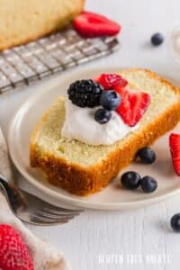 a close up of a slice of gluten free pound cake topped with whipped cream and berries