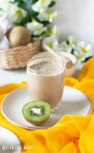 kiwi smoothie in a clear glass next to a slice of kiwi