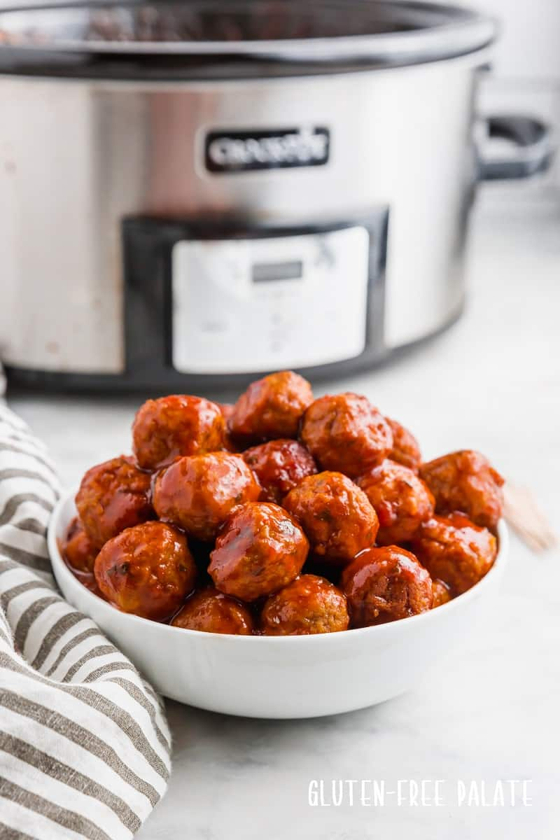 crockpot bbq meatballs in a white bowl in front of a crockpot